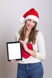 Adolescente lindo con el sombrero de Papá Noel que muestra la tableta Imagen de archivo