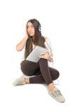 Adolescente lindo con música que escucha de los auriculares en la tableta Fotografía de archivo