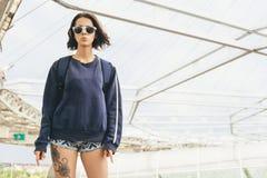 Adolescente lindo del inconformista en gafas de sol con el tatuaje en la pierna Foto de archivo libre de regalías
