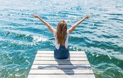 Adolescente lindo del joyfull que se sienta en pequeño muelle y que mira el río Imagen de archivo