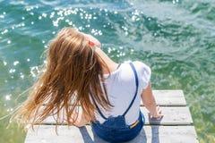 Adolescente lindo del joyfull que se sienta en pequeño muelle y que mira el río Imágenes de archivo libres de regalías