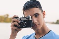 Adolescente lindo del muchacho con la cámara del telémetro del vintage Imagen de archivo