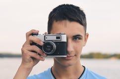 Adolescente lindo del muchacho con la cámara del telémetro del vintage Foto de archivo