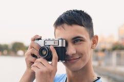 Adolescente lindo del muchacho con la cámara del telémetro del vintage Fotos de archivo libres de regalías