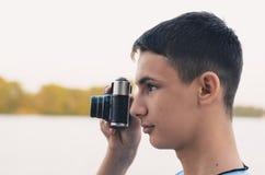 Adolescente lindo del muchacho con la cámara del telémetro del vintage Fotos de archivo