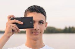 Adolescente lindo del muchacho fotografiado en un smartphone Fotografía de archivo