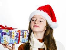 Adolescente lindo en el sombrero rojo de santa con la caja de regalo Imagen de archivo