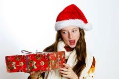 Adolescente lindo en el sombrero rojo de santa con la caja de regalo Imagen de archivo libre de regalías