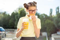Adolescente lindo en el uniforme escolar que sostiene una hamburguesa y un zumo de naranja Imagen de archivo