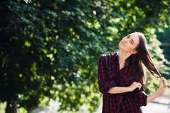 Adolescente lindo en la ropa informal que juega con sus trenzas, mirando la cámara y la sonrisa, oponiéndose a follaje verde Foto de archivo