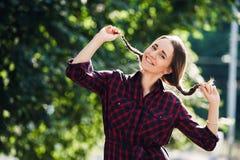 Adolescente lindo en la ropa informal que juega con sus trenzas, mirando la cámara y la sonrisa, oponiéndose a follaje verde Fotos de archivo