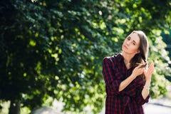 Adolescente lindo en la ropa informal que juega con sus trenzas, mirando la cámara y la sonrisa, oponiéndose a follaje verde Imágenes de archivo libres de regalías
