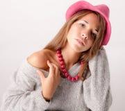 Adolescente lindo en sombrero y collar rosados Fotos de archivo