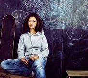 Adolescente lindo joven en sala de clase en el asiento de la pizarra en TA Imagenes de archivo