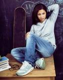 Adolescente lindo joven en sala de clase en el asiento de la pizarra en TA Imagen de archivo libre de regalías
