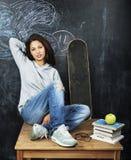 Adolescente lindo joven en sala de clase en el asiento de la pizarra en la tabla que sonríe, concepto moderno del inconformista,  Foto de archivo libre de regalías