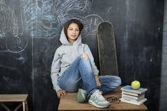 Adolescente lindo joven en sala de clase en el asiento de la pizarra en la sonrisa de la tabla Imagen de archivo