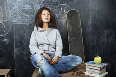 Adolescente lindo joven en sala de clase en el asiento de la pizarra en la sonrisa de la tabla Fotos de archivo libres de regalías