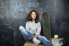 Adolescente lindo joven en sala de clase en el asiento de la pizarra en la sonrisa de la tabla Fotografía de archivo