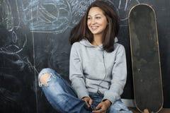 Adolescente lindo joven en sala de clase en el asiento de la pizarra en la sonrisa de la tabla Fotos de archivo