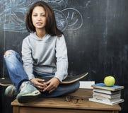 Adolescente lindo joven en sala de clase en el asiento de la pizarra en la sonrisa de la tabla Imágenes de archivo libres de regalías