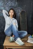 Adolescente lindo joven en sala de clase en el asiento de la pizarra en la sonrisa de la tabla Imagen de archivo libre de regalías