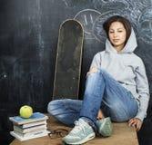 Adolescente lindo joven en sala de clase en el asiento de la pizarra en la sonrisa de la tabla Imagenes de archivo