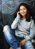 Adolescente lindo joven en sala de clase en el asiento de la pizarra en TA Fotos de archivo