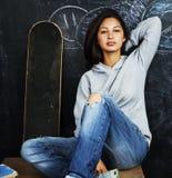 Adolescente lindo joven en sala de clase en el asiento de la pizarra en TA Imágenes de archivo libres de regalías