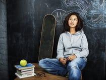 Adolescente lindo joven en sala de clase en el asiento de la pizarra en TA Imagen de archivo
