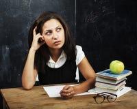 Adolescente lindo joven en sala de clase en el asiento de la pizarra en TA Foto de archivo