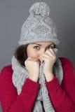 Adolescente lindo joven que se oculta en su bufanda cómoda del invierno Imagen de archivo