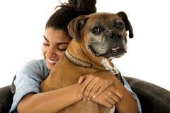 Adolescente lindo que abraza su perro un boxeador Fotografía de archivo libre de regalías
