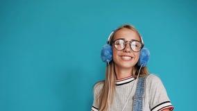 Adolescente lindo que baila y que se mueve a la música que escucha del ritmo en auriculares adentro dentro en el fondo azul mucha almacen de metraje de vídeo