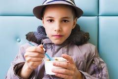Adolescente lindo que come el helado con el desmoche del chocolate Imagenes de archivo