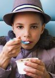 Adolescente lindo que come el helado con el desmoche del chocolate Imagen de archivo