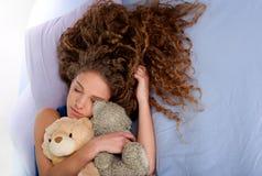 Adolescente lindo que duerme en la cama foto de archivo