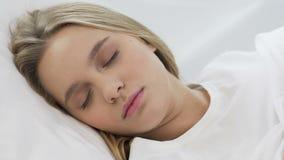 Adolescente lindo que duerme suavemente en el colchón ortopédico cómodo, primer metrajes