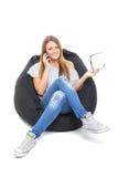 Adolescente lindo que habla en el teléfono que se sienta en el beanbag Foto de archivo libre de regalías