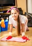 Adolescente lindo que hace la limpieza en la sala de estar Foto de archivo libre de regalías