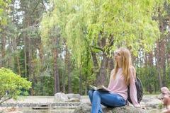 Adolescente lindo que lee un libro en el parque de la ciudad Fotografía de archivo libre de regalías