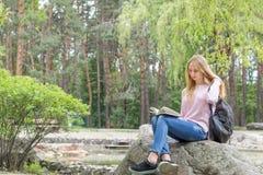 Adolescente lindo que lee un libro en el parque de la ciudad Fotos de archivo