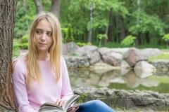 Adolescente lindo que lee un libro en el parque de la ciudad Imagen de archivo libre de regalías