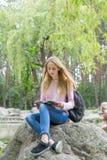 Adolescente lindo que lee un libro en el parque de la ciudad Fotos de archivo libres de regalías