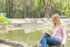 Adolescente lindo que lee un libro en el parque de la ciudad Imágenes de archivo libres de regalías