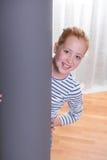 Adolescente lindo que mira de detrás un pilar Imagenes de archivo