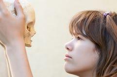 Adolescente lindo que mira el cráneo humano Imagen de archivo