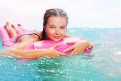Adolescente lindo que pone en matrass en el mar Fotografía de archivo