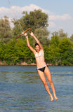Adolescente lindo que salta en el río Imagen de archivo