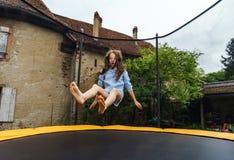 Adolescente lindo que salta en el trampolín Foto de archivo